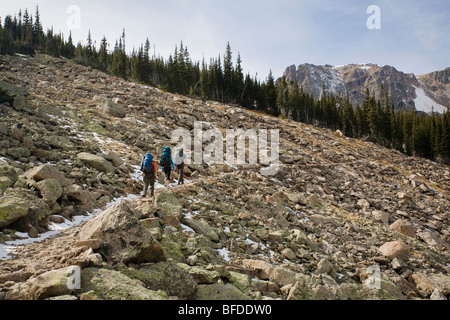 A man and two women hiking through a talus field on the Fern Lake Trail in Rocky Mountain National Park, Colorado. - Stock Photo