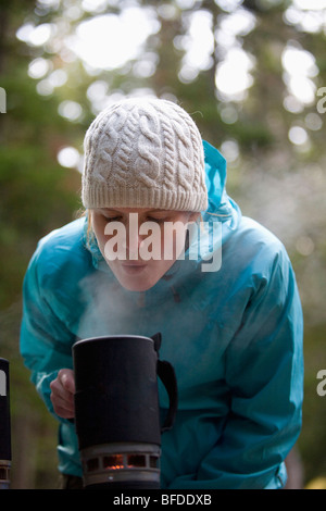 A woman blows into the pot of a camping stove while backcountry camping in Rocky Mountain National Park. - Stock Photo