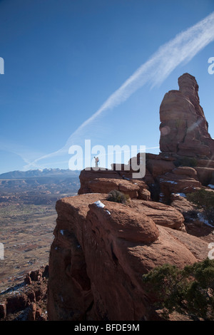 A male hiker standing above  a sandstone cliff overlooking Moab, Utah. - Stock Photo