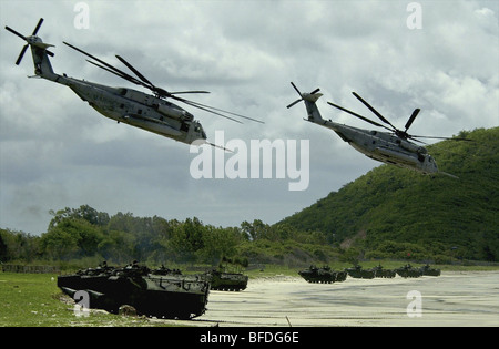 Helicopters fly over while amphibious vehicles land on a Thai beach during an assault demonstration - Stock Photo