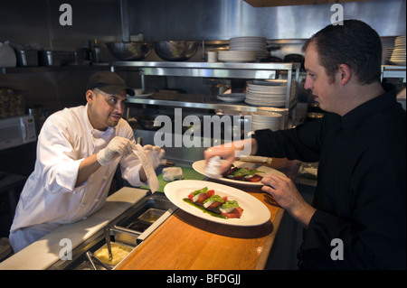 A hispanic worker works as a cook at an upscale Italian restaurant, Cucina Colore, in the Cherry Creek North area - Stock Photo