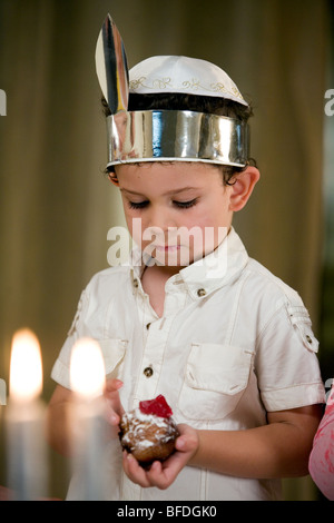 Boy holding a jelly doughnut, candles lit on the foreground. - Stock Photo