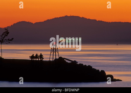 Silhouette of people on bench viewing sunset, Burrard Inlet, Vancouver, British Columbia, Canada - Stock Photo