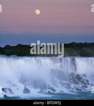 The American Falls at dusk with full moon rising over Niagara Falls State Park, Niagara Falls, New York, USA - Stock Photo