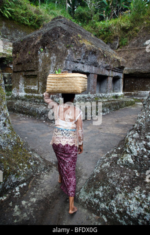 A Balinese woman carrying offerings in a basket at Gunung Kawi temple complex in Tampaksiring, Bali, Indonesia - Stock Photo