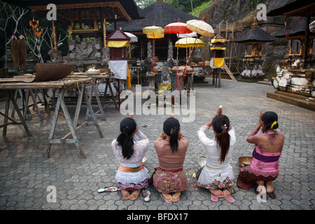 Balinese women praying at Gunung Kawi temple complex in Tampaksiring, Bali, Indonesia - Stock Photo