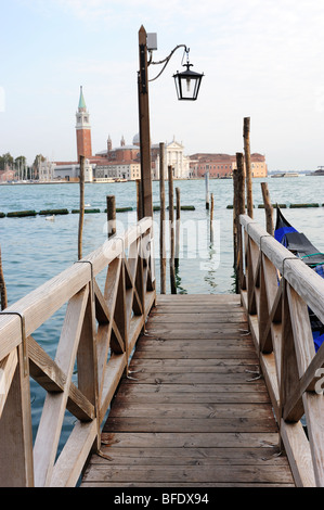 Looking along a wooden jetty by St Mark's Square with San Giorgio Maggiore in the background - Stock Photo