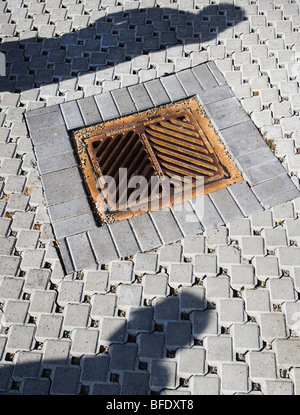 Two peoples shadows on a permeable surface roadway with storm drain. - Stock Photo