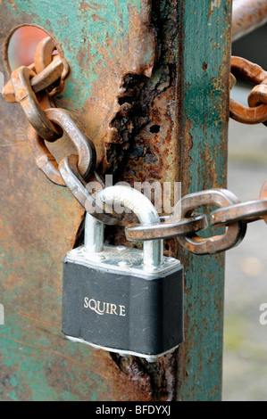 Padlock and rusty chain on old rusted metal gate - Stock Photo
