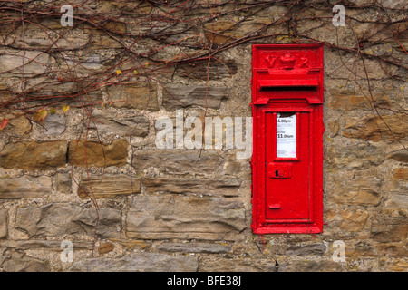 Post box on stone wall of a house in Thwaite, Swaledale Yorkshire Dales, England UK waiting for Christmas mail. - Stock Photo