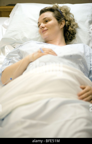 36 year old woman about to give birth lying in hospital bed, Chateauguay, Quebec, Canada - Stock Photo
