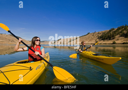A young couple enjoys a stunning day while kayaking on Trapp Lake, just south of Kamloops, British Columbia, Canada - Stock Photo