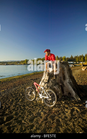 mountain biker relaxing and enjoying the view of Georgia Strait, Black Creek, Vancouver Island, British Columbia, - Stock Photo