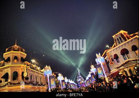 Main street and Magic Kingdom castle in Disneyland Paris at night winter Christmas Illuminations - Stock Photo
