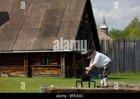 Costumed character tending a pot over a fire in Sainte-Marie Among Hurons settlement in town of Midland Ontario - Stock Photo