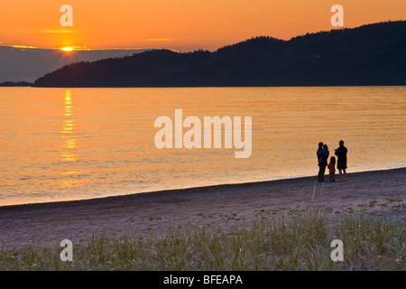 Family walking along the beach at Agawa Bay at sunset, Lake Superior, Lake Superior Provincial Park, Ontario, Canada - Stock Photo