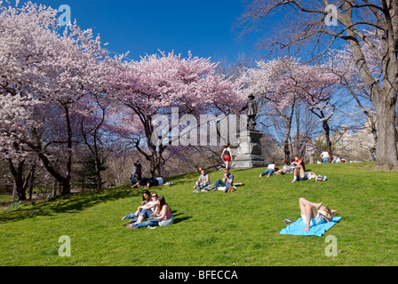 People relax on Pilgrim Hill in springtime in Central Park, New York City. - Stock Photo