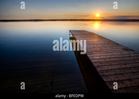 Sunset over a wooden wharf at Lake Audy, Riding Mountain National Park, Manitoba, Canada - Stock Photo