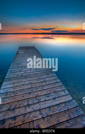 Sunset over a wooden wharf on Lake Audy, Riding Mountain National Park, Manitoba, Canada - Stock Photo