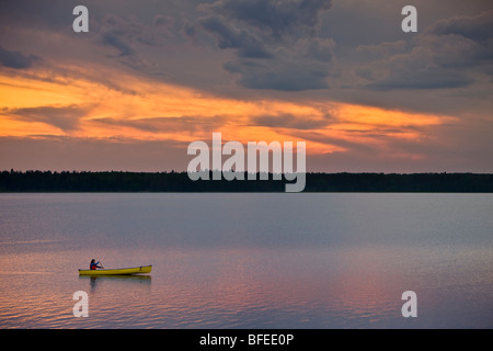 Canoeing on Lake Audy at sunset in Riding Mountain National Park, Manitoba, Canada - Stock Photo