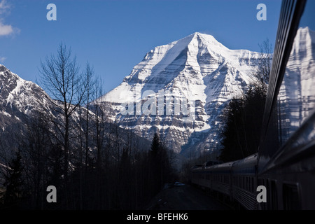 Passenger train passing in front of Mount Robson highest peak in Canadian Rocky Mountains located in Mount Robson - Stock Photo