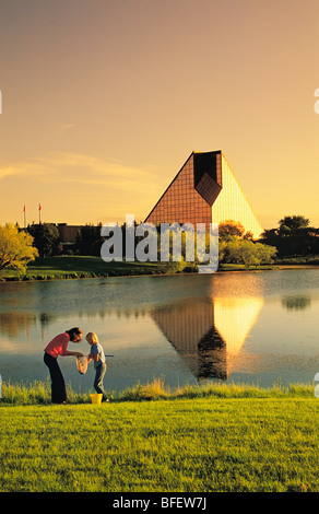 Two girls view water creatures collected from a pond in front of the Royal Canadian Mint, Winnipeg, Manitoba, Canada - Stock Photo