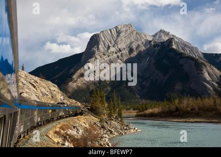 Passenger train riding along the Athabasca River in Jasper National Park, Alberta, Canada - Stock Photo
