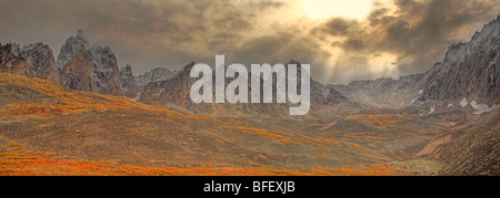 Clearing storm, sun rays poking through clouds and autumn colours in the Tombstone Valley in Tombstone Territorial - Stock Photo