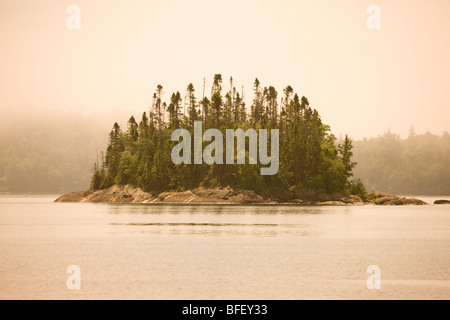 Island in fog in Warp Bay as seen from a canoe/kayak or hike-in campsite along Lake Superior Coastal Trail Lake - Stock Photo