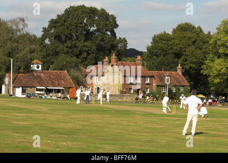 A quintessential English village green complete with a cricket match in play. - Stock Photo