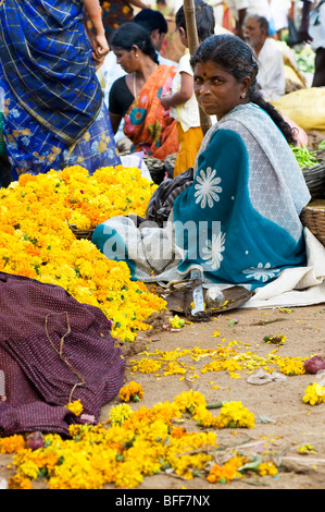 Woman selling flowers for celebratory religious garlands at market in  Puttaparthi, Andhra Pradesh, India - Stock Photo