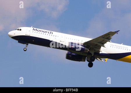 Airbus A3231 operated by Monarch Airlines climbing out from take off at Birmingham Airport - Stock Photo