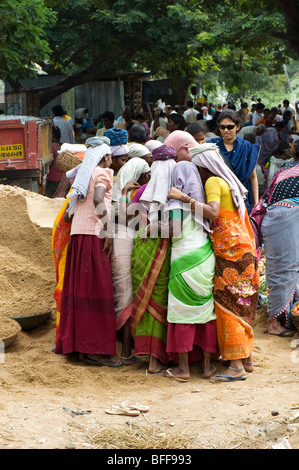Western tourist showing Indian female road workers a digital photo. Puttaparthi, Andhra Pradesh, India - Stock Photo