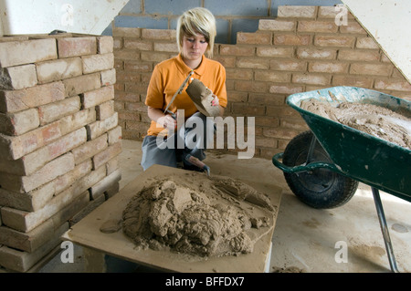 Girl student learning practical bricklaying at a City College - Stock Photo
