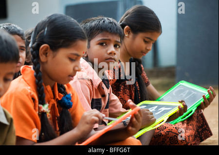 Indian school children sitting outside their school writing on chalkboards. Andhra Pradesh, India. Selective focus. - Stock Photo