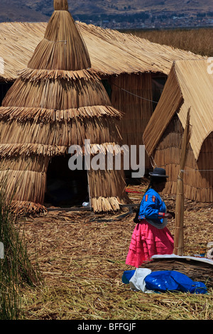 A female inhabitant infront of the huts made of reed on one of the Uros floating islands of Lake Titicaca - Stock Photo
