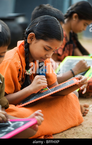 Indian school children sitting outside their school writing on chalkboards. Andhra Pradesh, India - Stock Photo