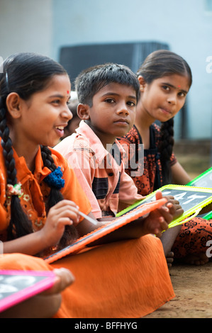 Indian school children sitting outside their school writing on chalkboards. Andhra Pradesh, India. Selective focus - Stock Photo