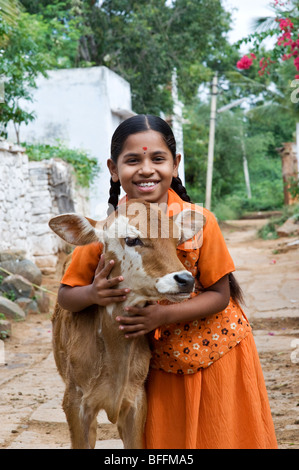 Young Indian village girl hugging a calf in a rural Indian village. Andhra Pradesh, India - Stock Photo