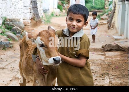 Young indian boy hugging a calf in a rural indian village. Andhra Pradesh, India - Stock Photo