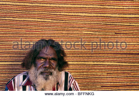 Aboriginal artist, Turkey Tolson Tjupurrula, with his work, Central Desert, Australia - Stock Photo
