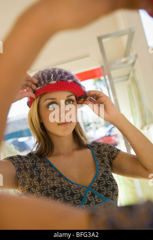 Young woman trying on hat in shop - Stock Photo