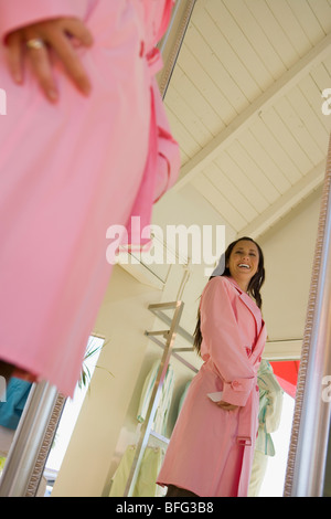 Young woman trying on pink trench coat in shop - Stock Photo