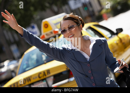 Businesswoman Hailing Cab using Cell Phone with hands free - Stock Photo