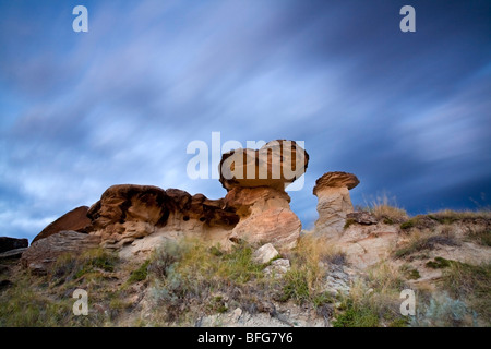 Fast moving clouds pass over hoodoos in Dinosaur Provincial Park in Alberta, Canada - Stock Photo