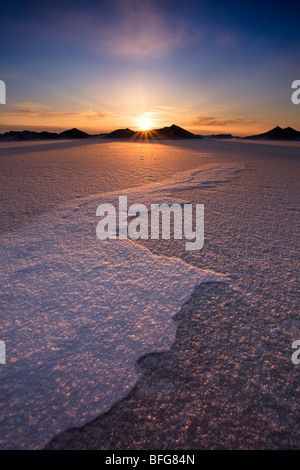 The sun sets behind mountains of pack ice on Lake Huron in Bayfield, Ontario, Canada - Stock Photo