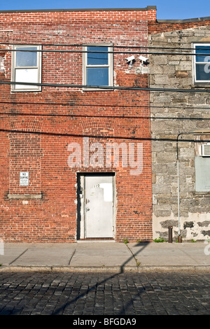 adjoining venerable old brick & stone buildings with clumsy patchwork alterations on cobblestone street in Red Hook - Stock Photo