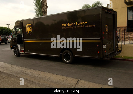 Brown UPS truck parked in front of a business making a rush delivery. - Stock Photo
