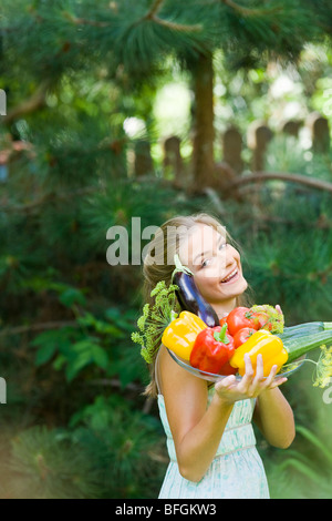 woman carrying plate with veggies - Stock Photo