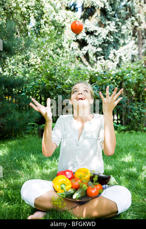 young woman with veggies in garden - Stock Photo